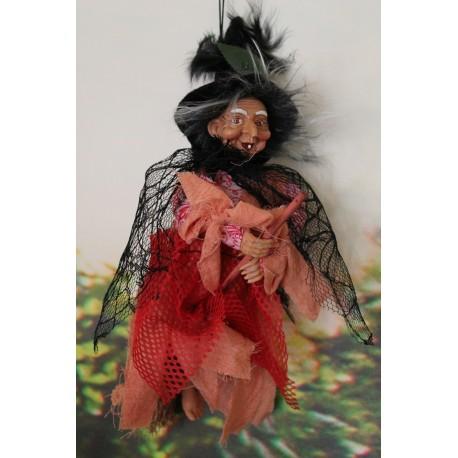 Jolie sorcière à cheval sur son balai faisant un joli sourire édenté en habit de coton coloré.
