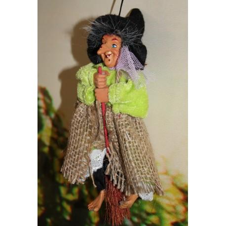 Petite sorcière sur son balai avec un tablier en toile de jute.