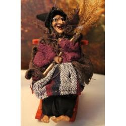 Jolie petite sorcière assise sur son rocking chair tenant un balai dans ses mains.